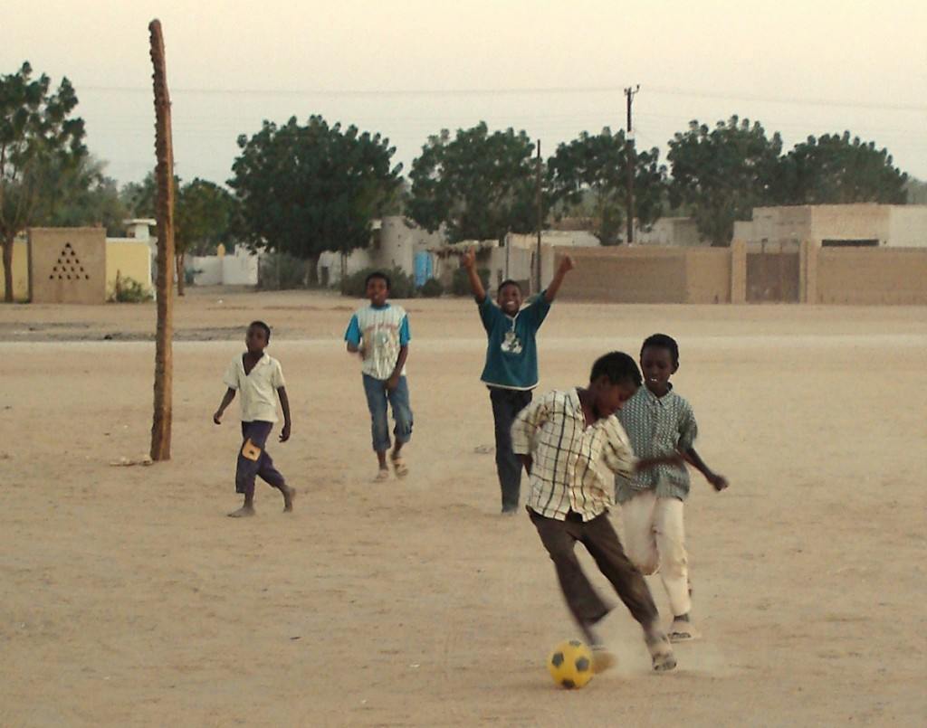 Kids in Sudan play on a dirt pitch. Photo: jay-chilli