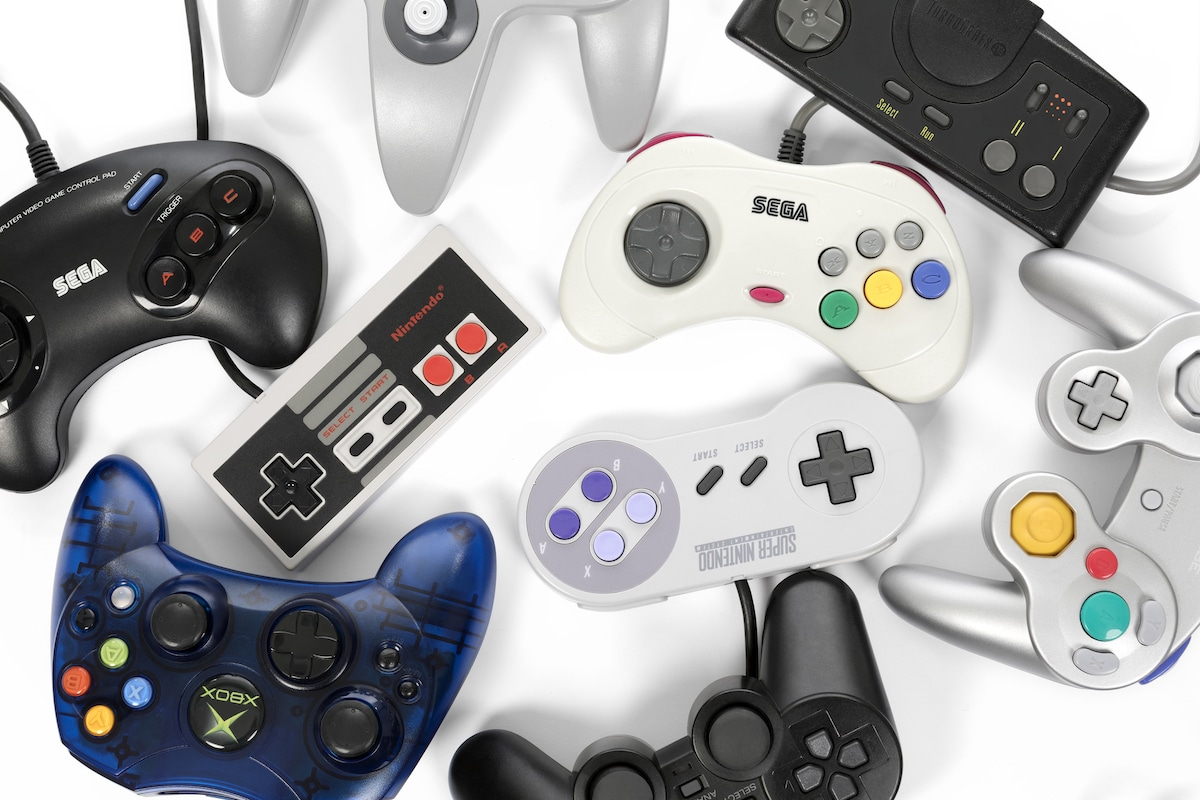 A collection of retro video game controllers shot from above on a white background.