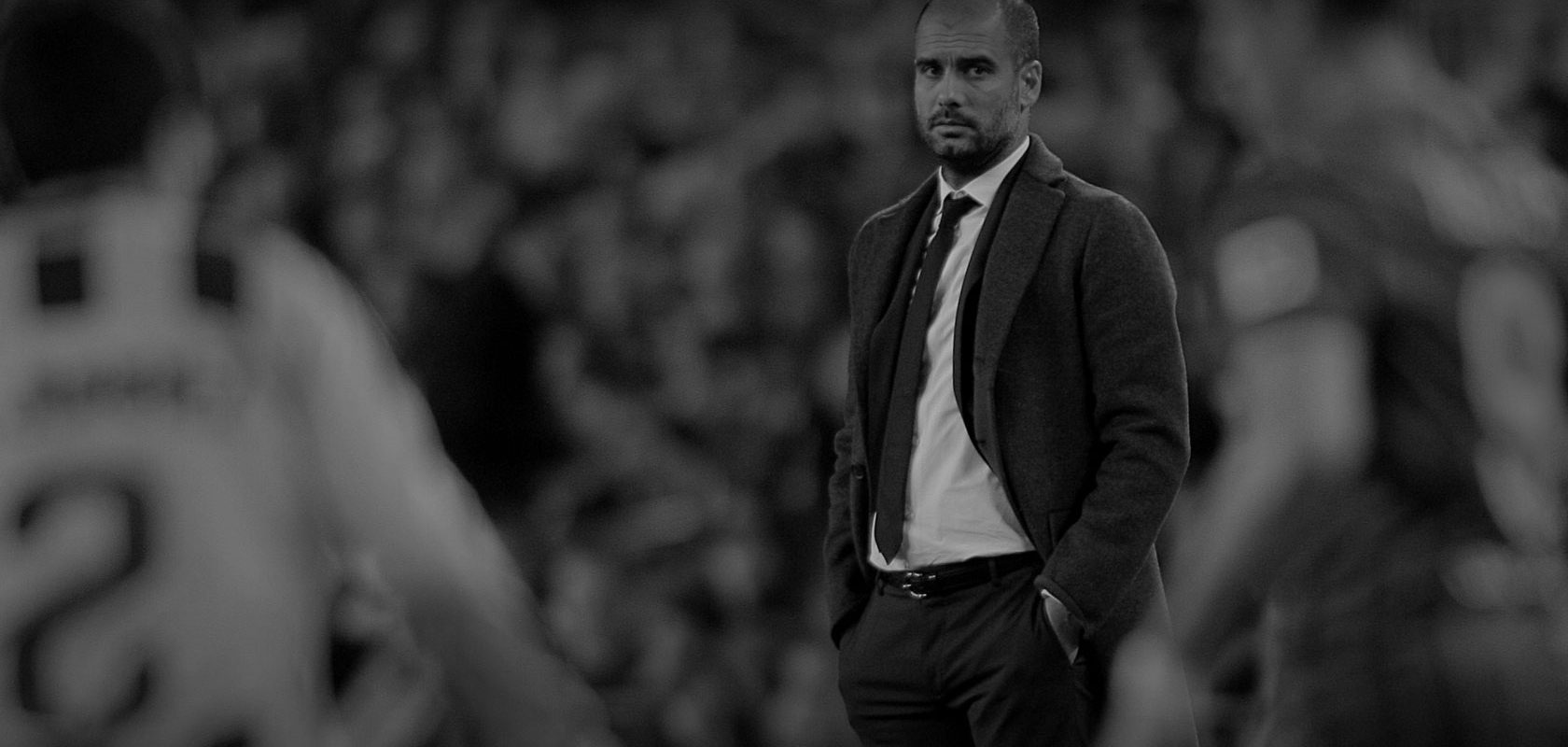 Pep Guardiola looks on from the sideline.
