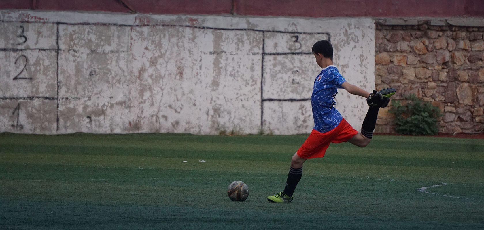 A lone soccer player strikes the ball. Photo: Yasar Kocal.
